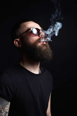 handsome Brutal bearded smoking man in sunglasses. Hipster tattoed boy with cigarette 写真素材