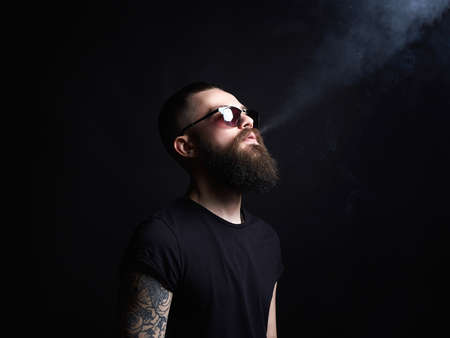 Brutal bearded man in sunglasses. Hipster, tattoed boy
