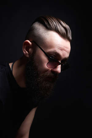 Man with stylish haircut. handsome Boy in sunglasses. Brutal bearded hipster in vintage leather aviator coat. Barber Shop