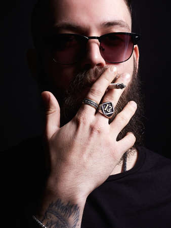 handsome Brutal bearded smoking man in sunglasses. Hipster tattoed boy with cigarette and rings on his hand