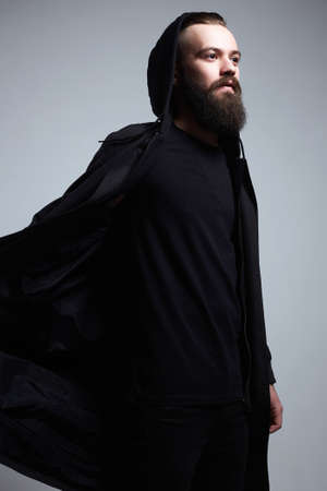 Fashion Man in black cloak and Hood. Bearded Handsome Boy. Stylish hipster