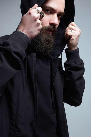 Bearded Handsome Man under Black Hood. Stylish model Boy. Fashion portrait