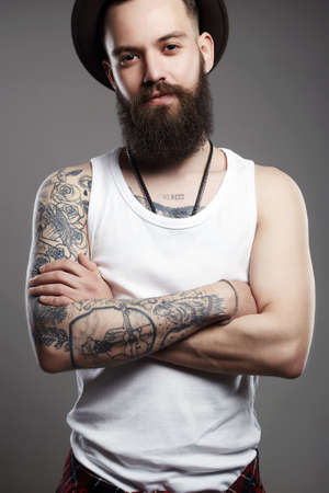 fashion Portrait of young bearded man. Smiling Hipster boy. handsome man in hat. Brutal bearded boy with tattoo Imagens