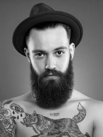 Black and white portrait of Bearded Man in Hat. Hipster boy with tattoo body