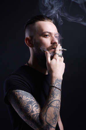 handsome Brutal bearded smoking man. Hipster tattoed boy with cigarette 写真素材 - 115372546