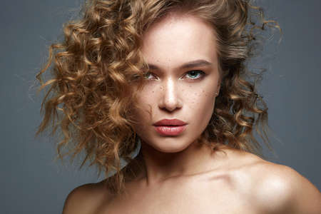 Beautiful freckles woman face. amazing curly girl with make-up. beauty fashion portrait. frizzle hair