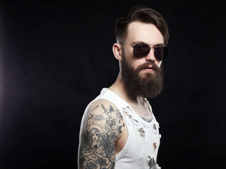 handsome man in sunglasses. bearded hipster in vintage torn dirty shirt. Boy, beard, haircut, tattoo