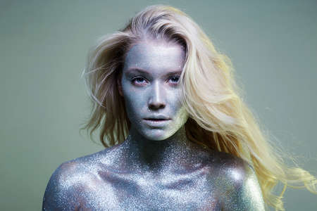 bright iridescent girl. Beautiful Young Woman with Sparkles on her Face and Body. Art Make-Up, in colorful light.