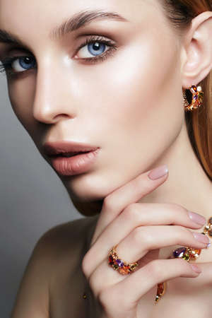 Gold jewelry on beautiful girl. young blonde woman with make-up and jewels accessories. Beauty Fashion Portrait Banque d'images
