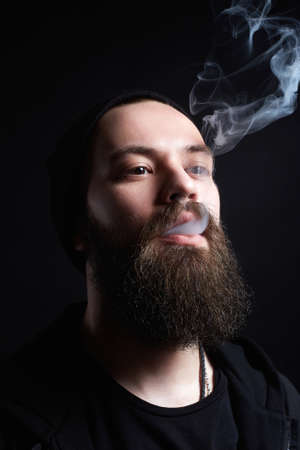 handsome bearded smoking man in Hat. Hipster boy doing shisha smoke