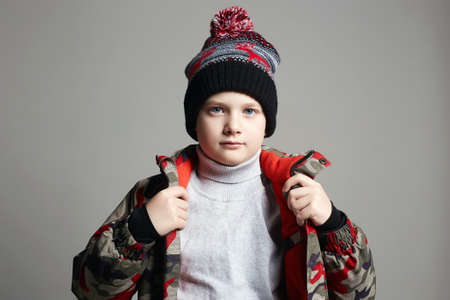 portrait of Fashionable Boy in winter outerwear. fashion kid. child. stylish teenager in hat and ski jacket