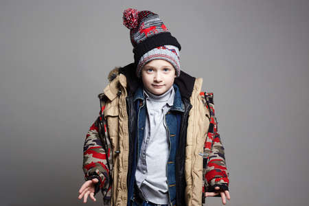 Funny Boy in winter outerwear. fashion kid. child. teenager wore all his clothes Imagens