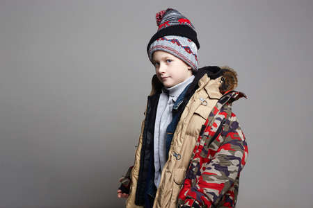 Funnu Boy in winter outerwear. fashion kid. child wore all his clothes