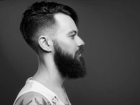 Retrato en blanco y negro de hombre guapo con barba y tatuaje. Chico hipster barbudo en camisa sucia desgarrada vintage Foto de archivo