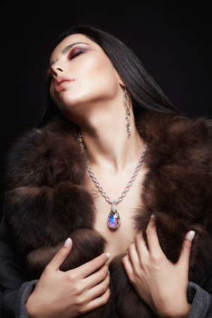 Bella ragazza castana in gioielli e pelliccia. Stile invernale donna in pelliccia di lusso. Trucco e accessori Archivio Fotografico
