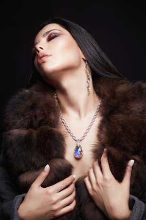 Belle fille brune en bijoux et fourrure. Femme de style hiver en fourrure de luxe. Maquillage et accessoires Banque d'images