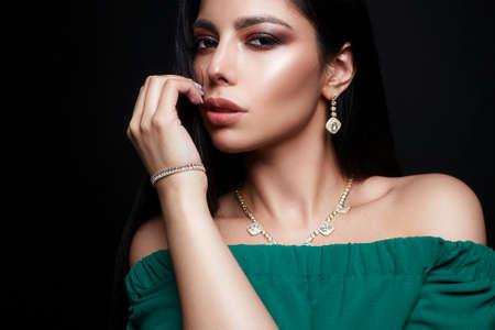 Hermosa chica morena en joyería y vestido verde. Mujer joven con maquillaje y accesorios
