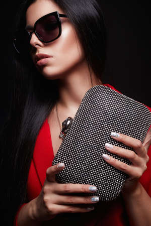 fashion portrait of Beautiful woman with clutch bag and sunglasses.jewelry. beauty girl