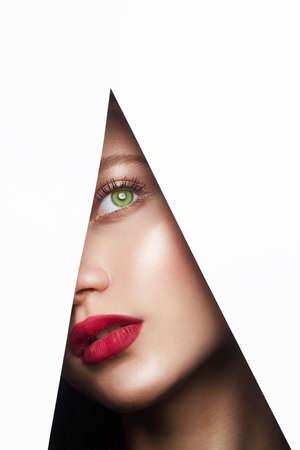 junge schöne Frau. weibliches Gesicht mit Make-up in Papierloch. Make-up Artist Konzept. Pfeile auf den Augen. Standard-Bild