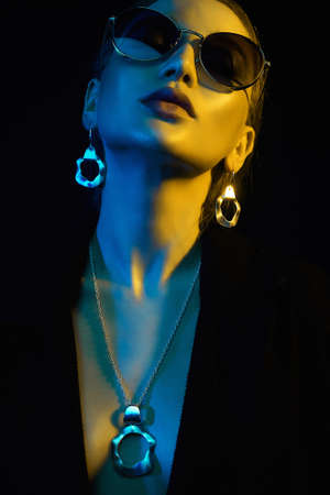 beauty young woman in colorful bright lights. Fashion portrait of beautiful girl in sunglasses and jewelry Stock Photo