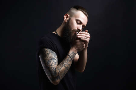 handsome Brutal bearded smoking man. Hipster tattoed boy with cigarette 写真素材