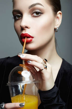 beautiful girl drinking fresh orange juice. Healthy young woman with make-up, holding plastic glass