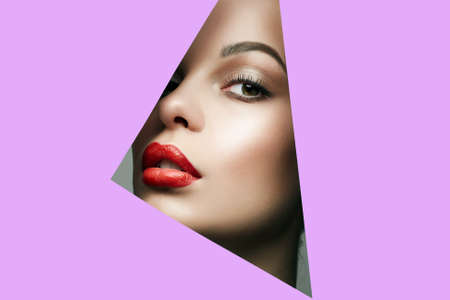 Beautiful red lips young woman into the hole of purple paper. Beautyportrait of  girl with make-up.