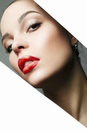 Beautiful red lips young woman into the hole of paper. Beauty portrait of  girl with make-up