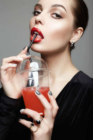 beautiful girl drinking cocktail. young brunette woman with make-up holding glass Imagens