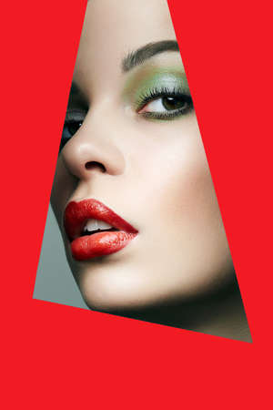 Beautiful red lips young woman into the hole of paper. Beauty portrait of  girl with make-up.