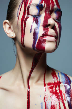 Girl with paint on her Face. liquid paint on beautiful face and Body. Color portrait of Woman in Paint