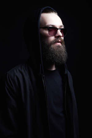 Handsome Man in Hood and sunglasses. Boy in a hoodie. portrait of bearded man