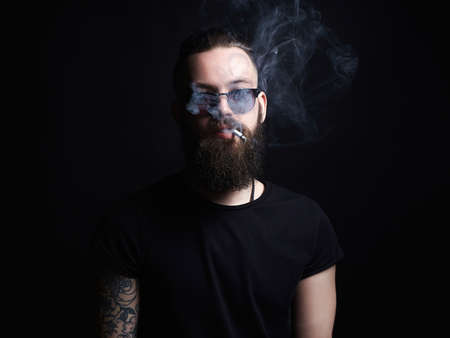 handsome smoking man. Hipster tattoed boy with cigarette. Brutal bearded man 写真素材