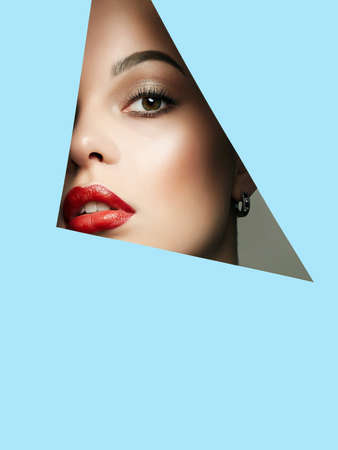 Beautiful red lips young woman into blue paper. Beauty portrait of  girl with make-up.