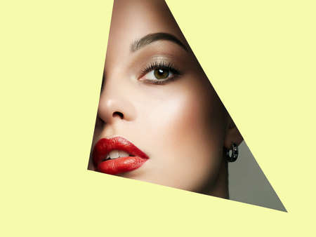 Beautiful red lips young woman into the hole of yellow paper. Beauty portrait of  girl with make-up.