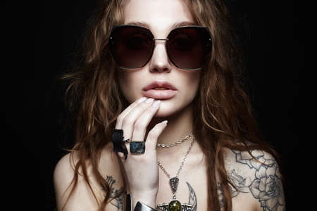 fashion portrait of Beautiful woman with tattoo. beauty tattooed girl in sunglasses and jewelry