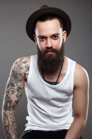 Tattooed handsome Smiling Man in Hat. Brutal hipster boy with tattoo Stok Fotoğraf