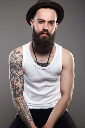 Tattooed handsome Man in Hat. Brutal hipster boy with tattoo