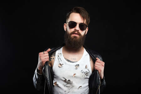 Brutal bearded Sexy boy in leather coat. fashionable tattooed handsome man in sunglasses Stok Fotoğraf
