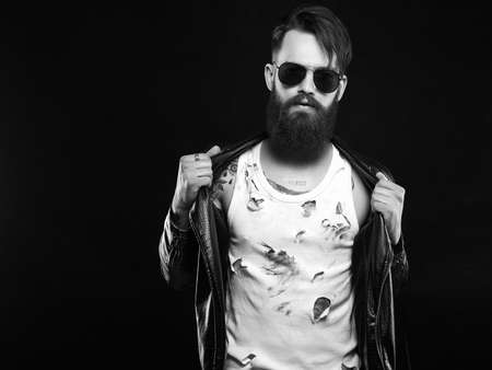 Black and white portrait. Brutal bearded Sexy boy in leather coat. fashionable tattooed handsome man in sunglasses Stok Fotoğraf