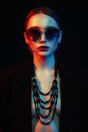 beauty young woman in colorful bright lights. Fashion portrait of beautiful girl in sunglasses and jewelry Stok Fotoğraf