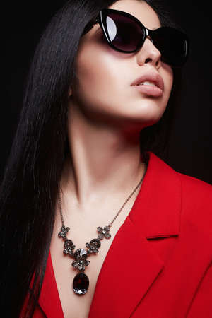 fashion portrait of Beautiful woman in sunglasses and jewelry. brunette girl in red