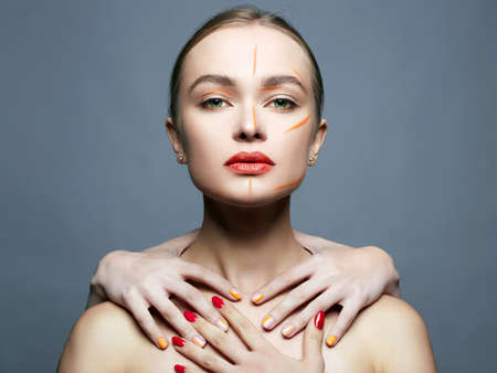 beautiful girl with someone elses hands on her neck. Beauty woman with orange paint make-up on her Face Stok Fotoğraf