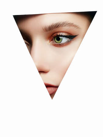 young beautiful woman with makeup into paper hole. make-up artist concept. arrows on the eyes.