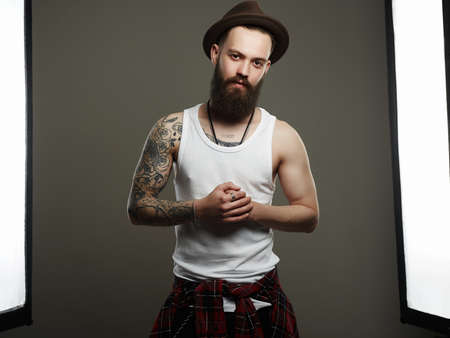 Tattooed handsome Bearded Man in Hat. Brutal hipster boy with tattoo. Male model in Photostudio