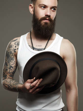 Tattooed handsome Bearded Man with Hat. Brutal hipster boy with tattoo. Male model in Photostudio