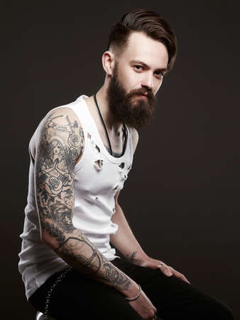 handsome man with beard. Brutal bearded hipster in vintage torn dirty shirt. Boy with stylish haircut and tattoo