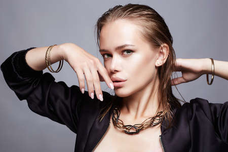 beautiful girl with jewelry. young wet hair style woman with golden accessories Stok Fotoğraf