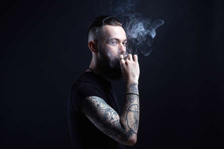 handsome bearded smoking man. Hipster tattoed boy with cigarette 写真素材
