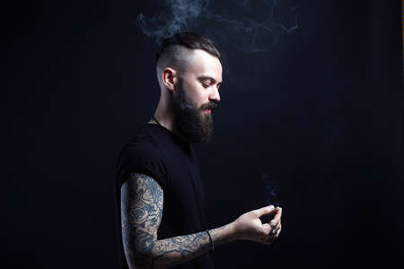 handsome bearded smoking man. Hipster tattoed boy with cigarette Banque d'images